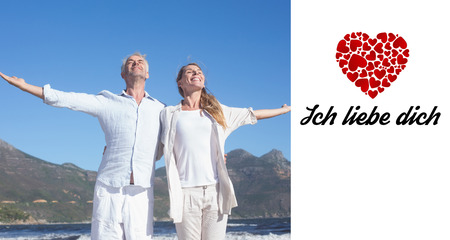 in liebe: Happy couple standing with arms outstretched at the beach against ich liebe dich