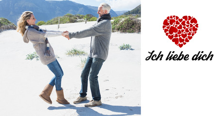 Liebe: Smiling couple spinning on the beach in warm clothing against ich liebe dich Stock Photo
