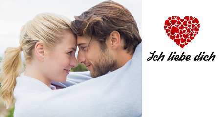 in liebe: Cute affectionate couple standing outside wrapped in blanket against ich liebe dich Stock Photo