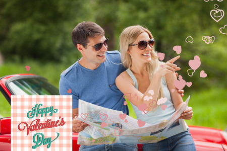 Cheerful young couple reading map against happy valentines day photo