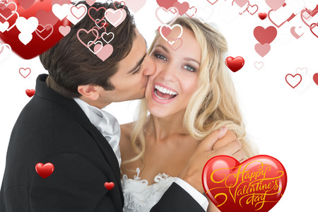 Handsome bridegroom kissing his wife on her cheek against happy valentines day photo