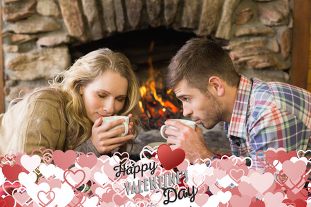 keeping room: Romantic couple drinking tea in front of lit fireplace against happy valentines day