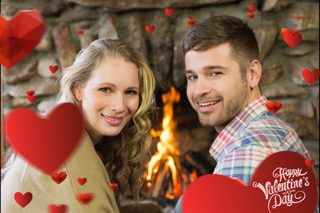 couple lit: Smiling young couple in front of lit fireplace against cute valentines message