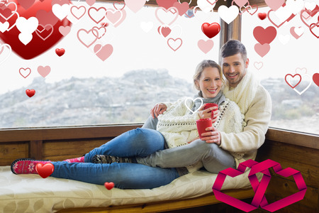 linking: Couple in winter wear with coffee cups against cabin window against linking hearts Stock Photo