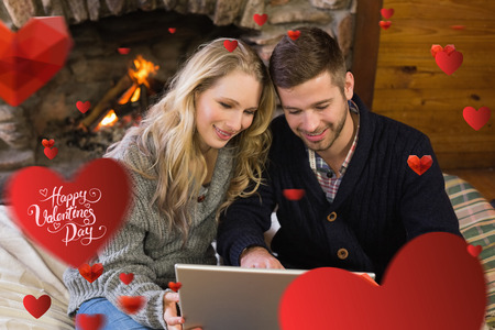 couple lit: Couple using laptop in front of lit fireplace against happy valentines day