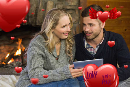 keeping room: Couple using tablet PC in front of lit fireplace against love is in the air