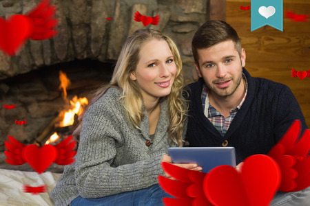 couple lit: Couple using tablet PC in front of lit fireplace against heart label