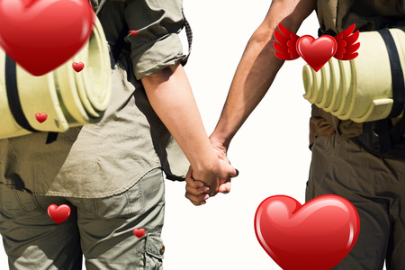 hitch hiker: Hitch hiking couple standing holding hands on the road against hearts Stock Photo