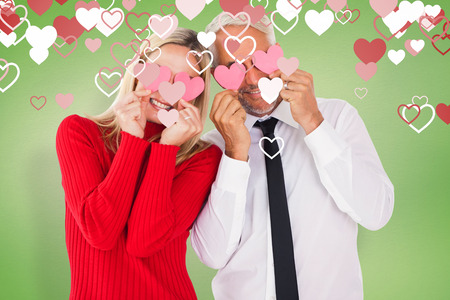 ttractive: Silly couple holding hearts over their eyes against green vignette