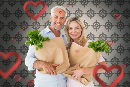 Happy couple carrying paper grocery bags against grey wallpaper photo