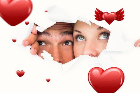 taken: Young couple peeking through torn paper against hearts