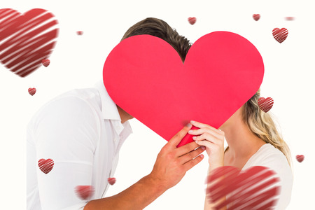 kissing couple: Attractive young couple kissing behind large heart against hearts