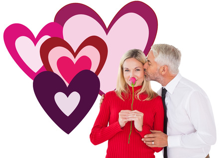 Handsome man giving his wife a kiss on cheek against valentines love hearts photo