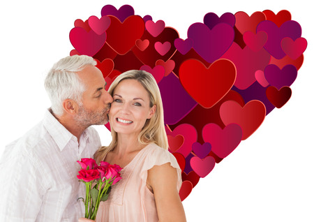 Affectionate man kissing his wife on the cheek with roses against heart photo