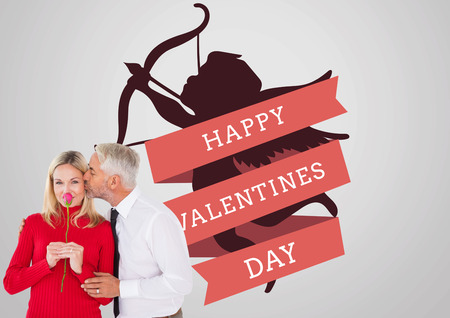 Handsome man giving his wife a kiss on cheek against valentines day greeting photo