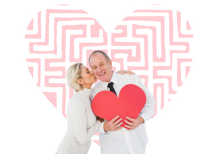 Older affectionate couple holding red heart shape against maze heart photo