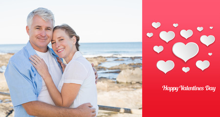 Happy casual couple embracing by the sea  against happy valentines day photo