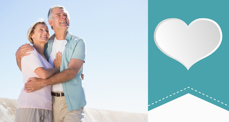 chinos: Happy senior couple embracing on the pier against heart label Stock Photo