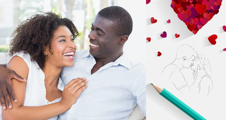 Attractive couple cuddling on the couch against sketch of kissing couple with pencil photo