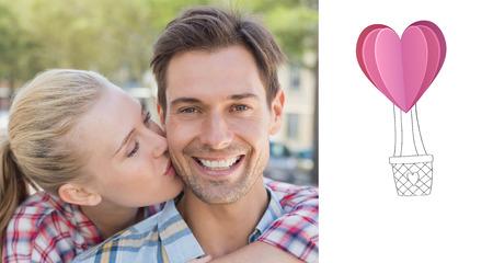 air kiss: Young hip woman giving boyfriend kiss on the cheek against heart hot air balloon