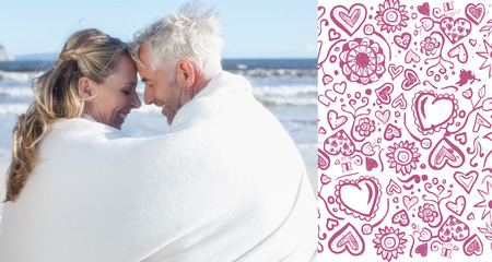 hair wrapped up: Couple sitting on the beach under blanket smiling at each other against valentines pattern