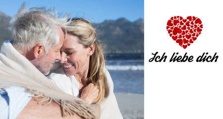 Liebe: Smiling couple sitting on the beach under blanket against ich liebe dich Stock Photo