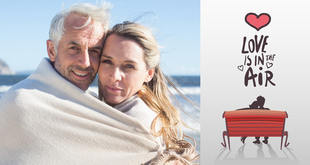 wrapped up: Smiling couple wrapped up in blanket on the beach against love is in the air