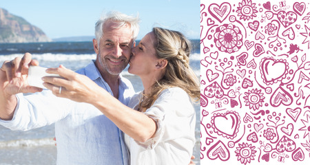 Married couple at the beach together taking a selfie against valentines pattern photo
