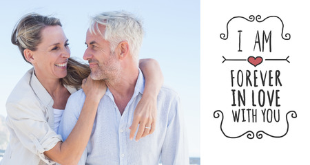 Attractive married couple hugging at the beach against valentines message photo