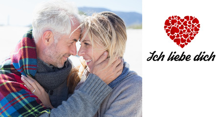hair wrapped up: Happy married couple embracing on the beach against ich liebe dich Stock Photo