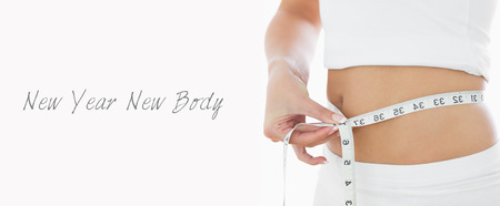 body concern: Closeup midsection of woman measuring waist over white background Stock Photo