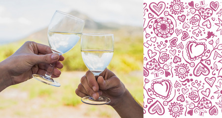clinking: Couple clinking wine glasses outside against valentines pattern