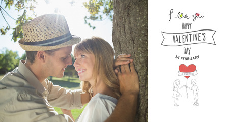 Cute smiling couple leaning against tree in the park against happy valentines day photo