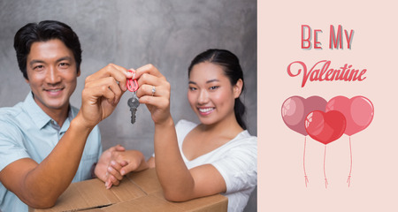 Happy couple holding house key and leaning on moving box against cute valentines message photo