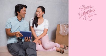 Happy couple sitting on floor using tablet surrounded by boxes against happy valentines day photo