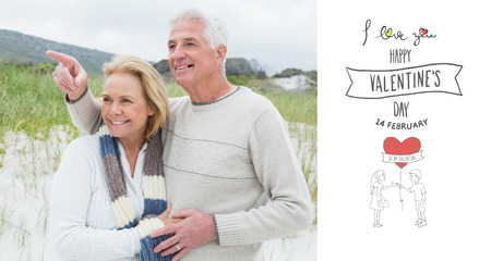 Cheerful romantic senior couple at beach against happy valentines day photo