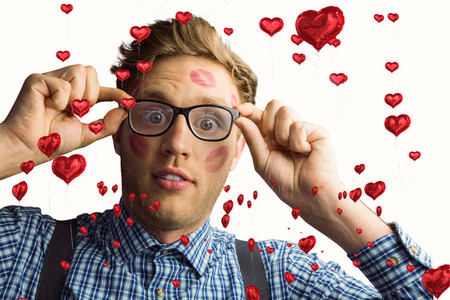 Geeky hipster covered in kisses against red heart balloons floating photo