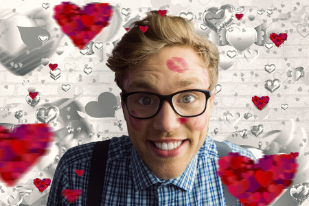 Geeky hipster covered in kisses against grey valentines heart pattern photo