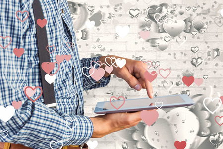 Geeky businessman using his tablet pc against grey valentines heart pattern photo