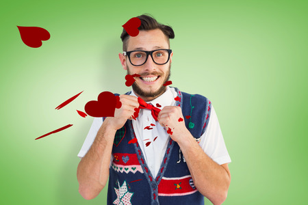 tightening: Geeky hipster wearing christmas vest against green vignette Stock Photo