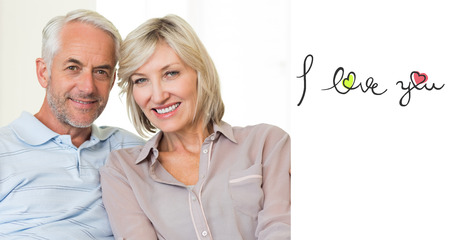 arm around: Smiling mature couple sitting on sofa with arm around against i love you Stock Photo