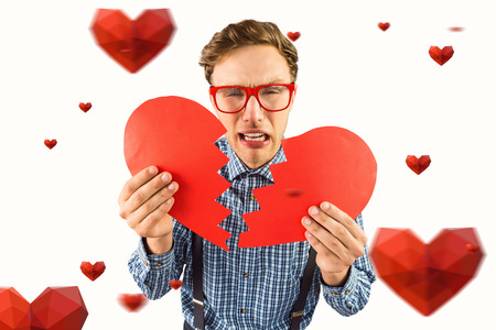 broken love: Geeky hipster holding a broken heart  against hearts Stock Photo