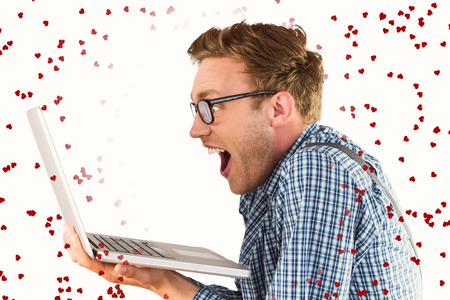 geeky: Geeky businessman using his laptop against red love hearts