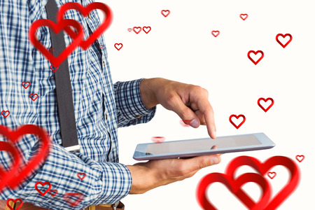 Geeky businessman using his tablet pc against hearts photo