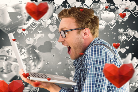 funny love: Geeky businessman using his laptop against grey valentines heart pattern