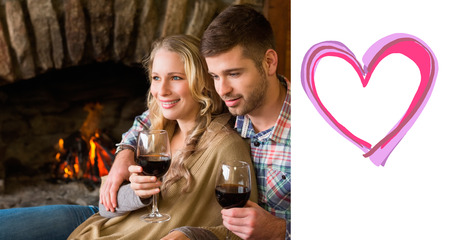 couple lit: Couple with wineglasses in front of lit fireplace against heart Stock Photo