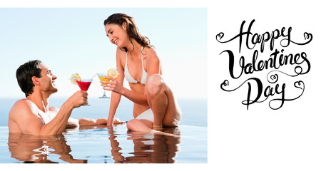 Couple having cocktails in the pool against happy valentines day photo