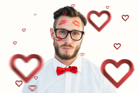 lustful: Geeky hipster with kisses on his face against hearts Stock Photo