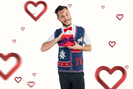 geeky: Geeky hipster offering christmas gift against hearts