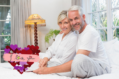 Portrait of a relaxed happy mature couple with book in bed against i love you Banco de Imagens
